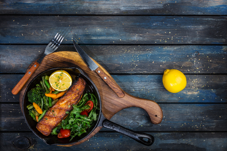 Grilled salmon fillet in a frying pan, vegetables, arugula with a lemon. Stock Photo
