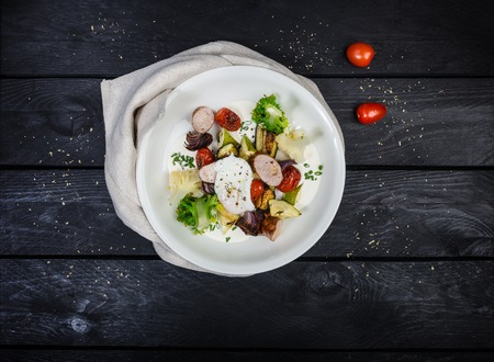 Salad of grilled vegetables with sausages and poached egg. Standard-Bild