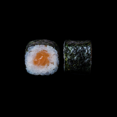 Sushi. Roll with salmon in nori leaf, isolated in black background