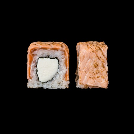 Sushi. Roll with seared salmon and cream cheese, isolated in black background