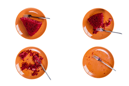 Top View. Eating process of delicious Red velvet cake on a ceramic plate with a fork. Isolated on the white background Archivio Fotografico