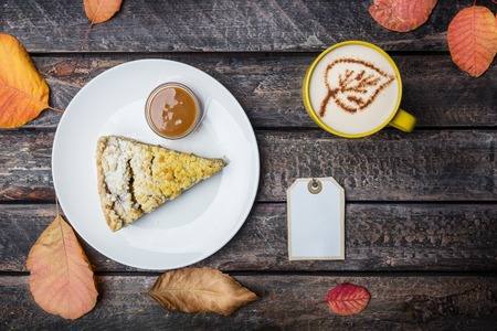 Apple pie with coffee on a white dish, on a beautiful wooden background. Top view autumn leaves.