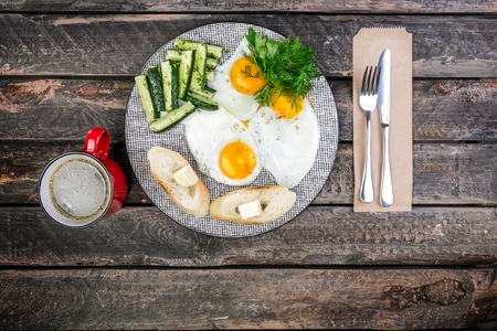 Tasty breakfast in the morning. Scrambled eggs and pickled cucumbers and salad with sauerkraut. Served by cutlery, with bread, butter and filter coffee. Top view Standard-Bild
