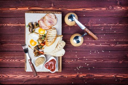 Big breakfast. Ham, bread toast, fried eggs, grilled mushrooms and tomatoes with sauce. There is a pepper grinder and cutlery. Top view