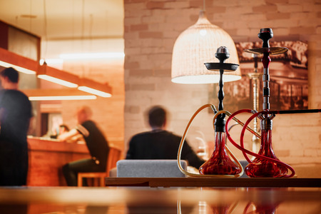 Hookahs in a warm interior, against the background of people sitting