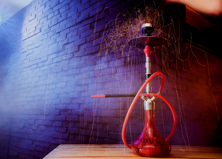 Red shisha hookah with smoke and red sparks on wood table brick, art background. Shisha Concept
