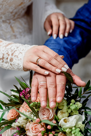 Hands with wedding gold rings happy newlyweds on a the bouquet background. close-up