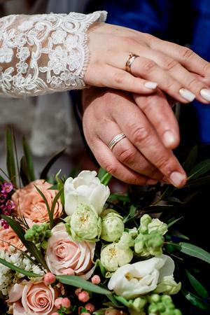 Hände mit Hochzeit Goldringe glücklich Jungvermählten auf einem Hintergrund Bouquet . Nahansicht Standard-Bild - 98639465