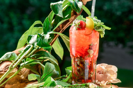 refreshing cocktail with ice, mint, lemon and strawberries on the nature green  background. isolated. space. close up.