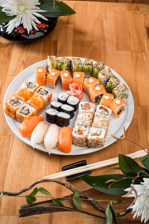 Rolls with salmon, eel, avocado and tuna on a white plate isolated on an orange background. close-up. Japanese cuisine. Stock fotó