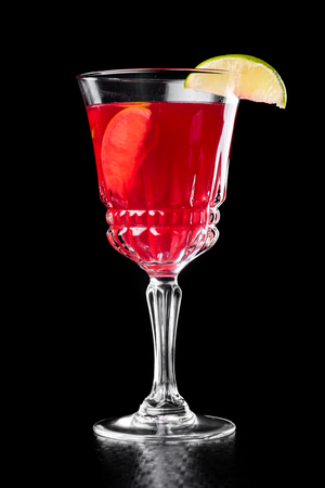 Beautiful red cocktail in a beautiful glass isolated on a black
