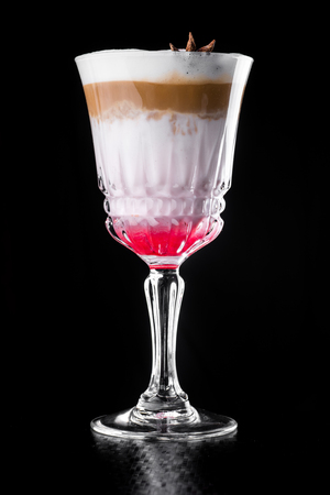 Hot Coffee layered Cocktail isolated on black in a beautiful glass Stock fotó