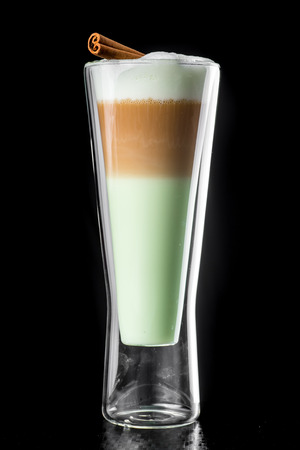 Hot Coffee layered Cocktail isolated on black in a beautiful glass, green liquor.