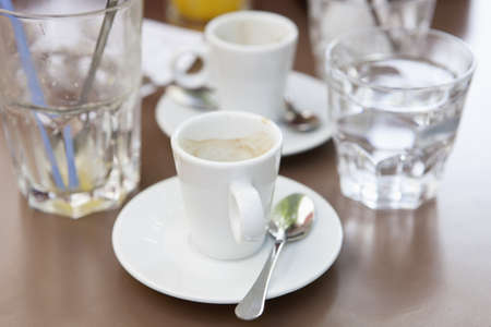 Empty glass of orange juice,empty cup of expresso and the bill on a table in a Bistrot Stock Photo - 15917832