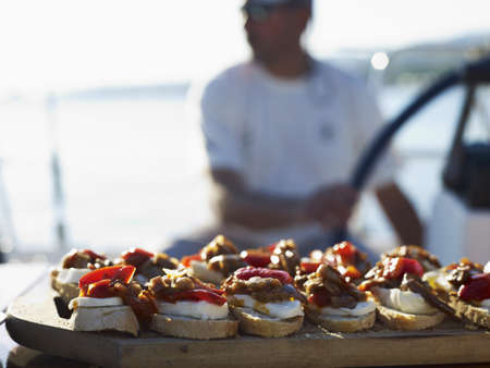 Peppers and cheese on sliced bread :appetizers on a boat