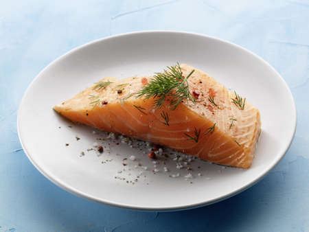 Thick piece of raw salmon with dill and pink peppercorns