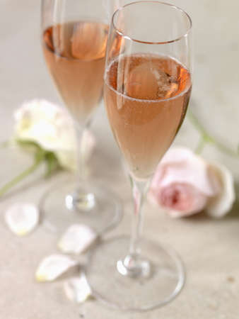 Two glasses of rosé Champagne and roses