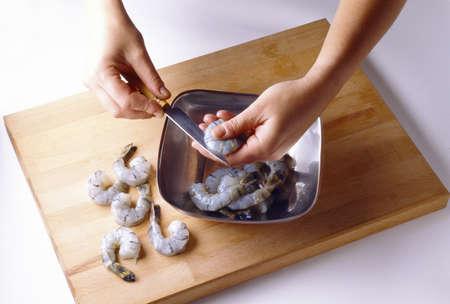Slicing the raw shrimp in half
