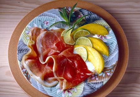 Raw ham with sliced mangoes