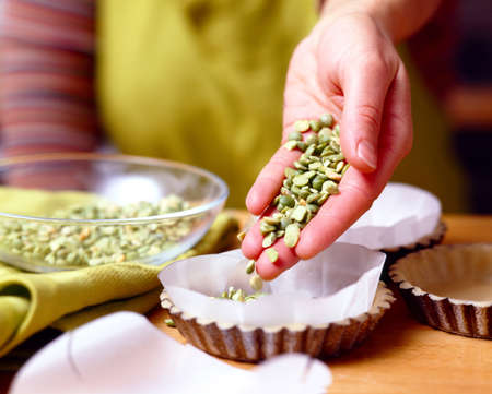 food: Placing the dried beans on the wax paper in the moulds