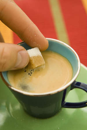 Putting a sugarlump in a cup of coffee Stock Photo - 17026823