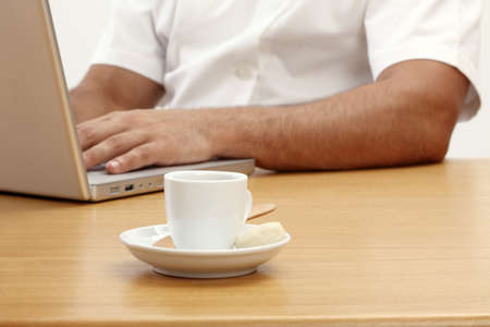 Having a cup of coffee sitting at a desk by the computer Stock Photo - 17027153