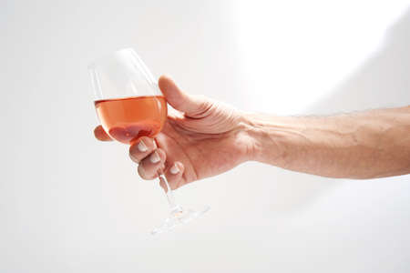 Person holding a glass of rosé wine Stock Photo - 17025993