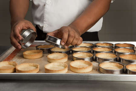 Cook turning out the tartlet bases Stock Photo - 17027560