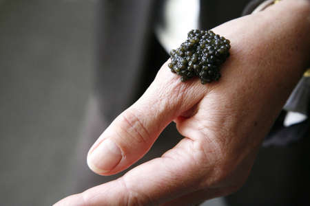 spoonful: Placing a spoonful of caviar on a hand to taste