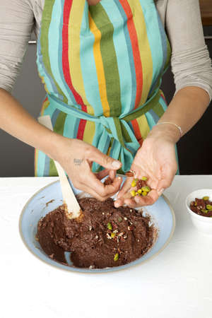 Adding the dried fruit to the chocolate paste Stock Photo - 17028091