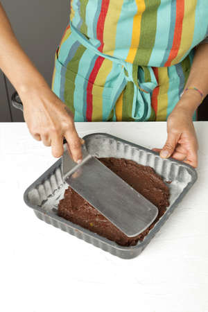Spreading out the chocolate paste in the mould Stock Photo - 17028093