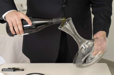 Wine waiter decantering a bottle of red wine