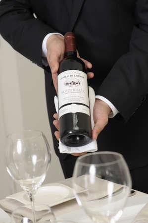 Wine waiter presenting a bottle of red wine LANG_EVOIMAGES