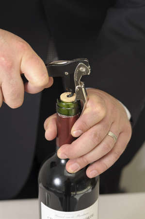 Wine waiter opening a bottle of red wine LANG_EVOIMAGES