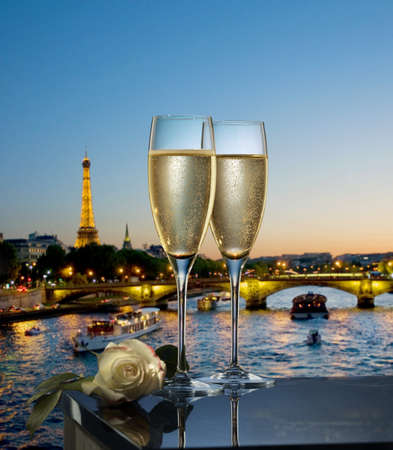 Two glasses of Champagne infront of a view of the Seine in Paris LANG_EVOIMAGES