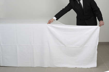 buffet table: Placing a tablecloth on a buffet table