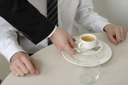 Waiter serving a coffee to a person sitting at a table Stock Photo - 17029112