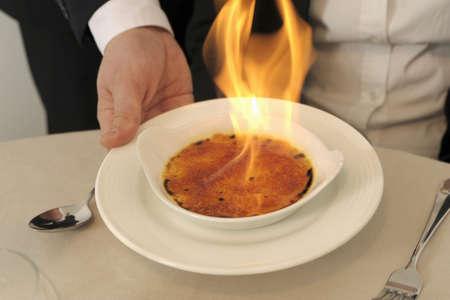 Caramelizing a crème brûlée Stock Photo - 17029116