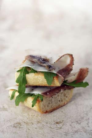 Lardo di colonnata,anchovies and rocket lettuce on bread Stock Photo - 17029239