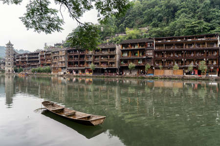 Ancient Old Wooden Apartments Of Feng Huang Phoenix City With A Boat In Foreground