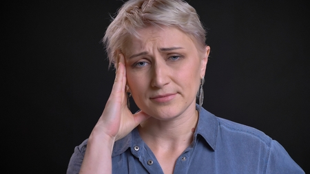 Closeup portrait of adult attractive caucasian female having a headache and being tired while looking at camera with background isolated on black
