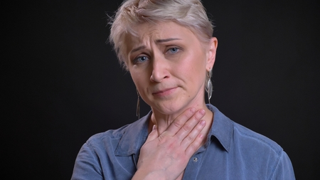 Closeup portrait of adult attractive caucasian female having a sick throat and being ill while looking at camera with background isolated on black Stock Photo