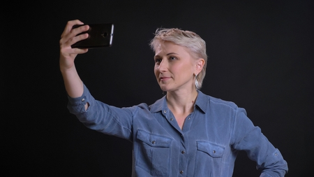 Closeup portrait of adult caucasian female with short blonde hair taking selfies on the phone with background isolated on black