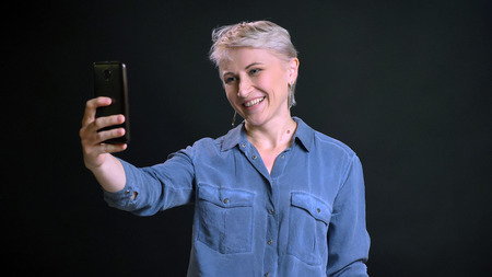 Closeup portrait of adult cheerful caucasian female with short blonde hair making selfies on the phone and smiling in front of the camera Stock Photo