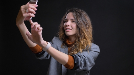 Closeup shoot of young attractive caucasian female taking selfies on the phone in front of the camera with background isolated on black Фото со стока