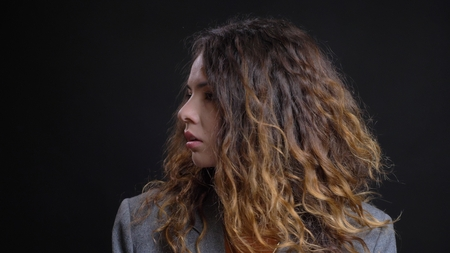 Closeup profile shoot of young pretty caucasian female with brunette curly hair looking forward with background isolated on black