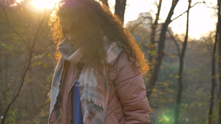 Portrait of beautiful curly-haired caucasian girl walking in autumnal park and watching downwards.