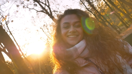 Selfie-photo of cute curly-haired caucasian girl with inclined head watching happily into camera in sunny autumnal park.