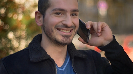 Portrait of caucasian man joyfully talking on smartphone and looking leftwards on street background.