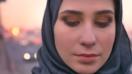 Closeup shoot of young attractive female face in hijab looking straight down with urban city on the background